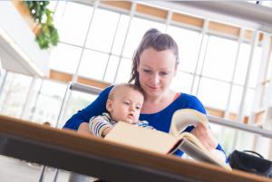 Eine studierende Mutter liest mit Baby auf dem Schoß in der Zentralbibliothek. Foto: Universität Passau/Studentenwerk Niederbayern/Oberpfalz