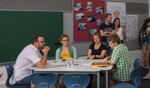 Personen sitzen in einer Gruppe und denken über Mathematik-Aufgabe nach.
