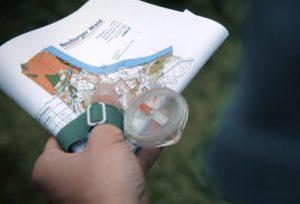 Teilnehmender beim Orientierungslauf mit Karte und Kompass