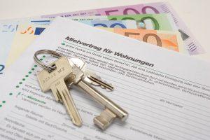 Symbolbild eines Mietvertrags mit Wohnungsschlüssel und Geldscheinen
