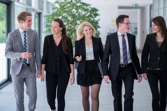 Studierende laufen einen Gang entlang und unterhalten sich angeregt